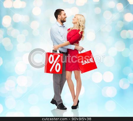 happy couple with red shopping bags stock photo, people, sale, discount and christmas concept - happy couple with red shopping bags hugging over blue holidays lights background by Syda Productions