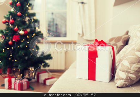 gift box on coach at home stock photo, christmas, x-mas, holidays, winter and happiness concept - gift box on coach at home by Syda Productions