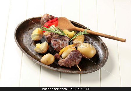 Beef shish kebab  stock photo, Beef shish kebab and new potatoes on cast iron plate by Digifoodstock