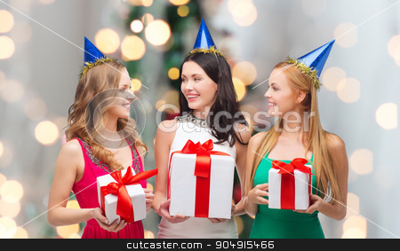 smiling women in party caps with gift boxes stock photo, presents, holidays, people and celebration concept - smiling women in party caps with gift boxes over christmas tree lights background by Syda Productions