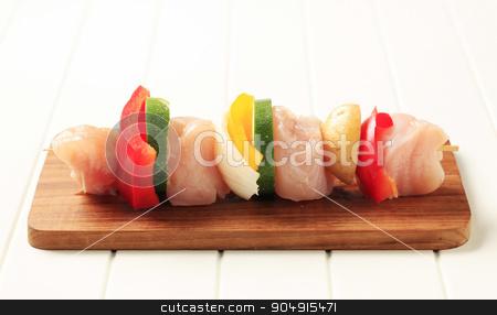 Raw chicken shish kebab stock photo, Raw chicken shish kebab on a cutting board by Digifoodstock