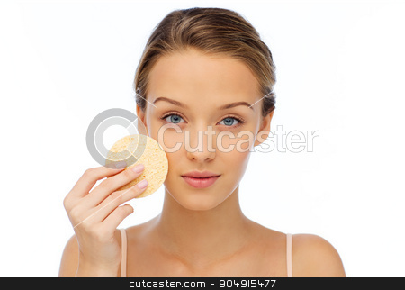 young woman cleaning face with exfoliating sponge stock photo, beauty, people and skincare concept - young woman cleaning face with exfoliating sponge by Syda Productions