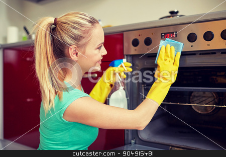 happy woman cleaning cooker at home kitchen stock photo, people, housework and housekeeping concept - happy woman with bottle of spray cleanser cleaning oven at home kitchen by Syda Productions