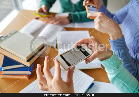 students with smartphones making cheat sheets stock photo, people, education, technology and exam concept - close up of students with smartphones taking picture of books page and making cheat sheet in school library by Syda Productions