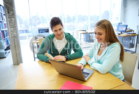 happy students with laptop and books at library stock photo, people, education, technology and school concept - happy students with laptop computer and books in library by Syda Productions