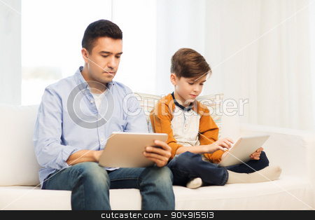 father and son with tablet pc at home stock photo, leisure, technology, technology, family and people concept - father and son with tablet pc computer networking or playing at home by Syda Productions