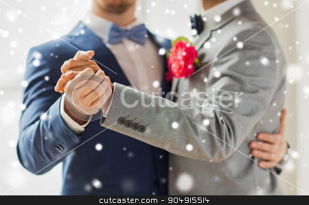 close up of happy male gay couple dancing stock photo, people, homosexuality, same-sex marriage and love concept - close up of happy male gay couple holding hands and dancing on wedding over snow effect by Syda Productions