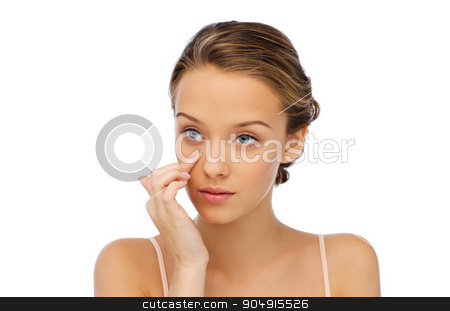 young woman applying cream to her face stock photo, beauty, people, cosmetics, skincare and health concept - young woman applying cream to her face by Syda Productions