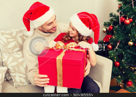 smiling father and daughter opening gift box stock photo, family, christmas, x-mas, winter, happiness and people concept - smiling father and daughter in santa helper hats opening gift box by Syda Productions