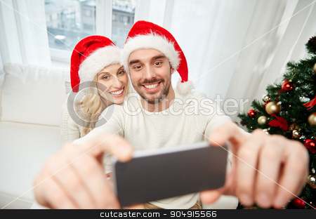 couple taking selfie with smartphone at christmas stock photo, christmas, holidays, technology and people concept - happy couple in santa hats taking selfie picture with smartphone at home by Syda Productions