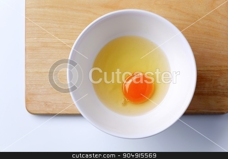 Raw egg stock photo, Raw egg white and yolk in a bowl - overhead by Digifoodstock