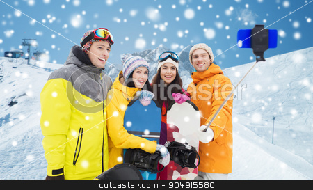 happy friends with snowboards and smartphone stock photo, winter sport, leisure, friendship, technology and people concept - happy friends with snowboards and smartphone taking selfie over snow and mountain background by Syda Productions