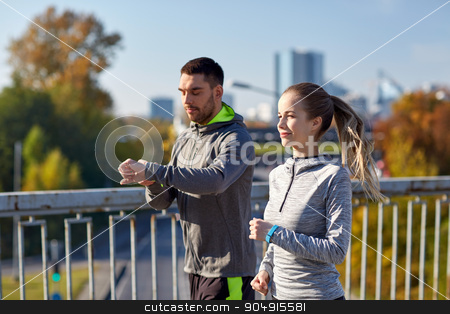 couple running over city highway bridge stock photo, fitness, sport, people, technology and healthy lifestyle concept - smiling couple with heart-rate watch running over city highway bridge by Syda Productions