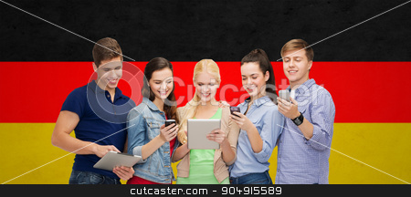 smiling students using smartphones and tablet pc stock photo, people, education and modern technology concept - smiling students using smartphones and tablet pc computer over german flag background by Syda Productions