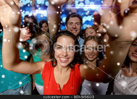 smiling women dancing in club stock photo, party, holidays, celebration, friends and people concept - smiling friends dancing and waving hands in club and snow effect by Syda Productions
