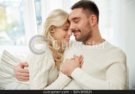 happy couple covered with plaid on sofa at home stock photo, family, love, winter, holidays and people concept - happy couple covered with plaid sitting on sofa at home by Syda Productions