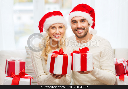 happy couple at home with christmas gift boxes stock photo, christmas, holidays and people concept - happy couple in santa hats with gift boxes sitting on sofa at home by Syda Productions