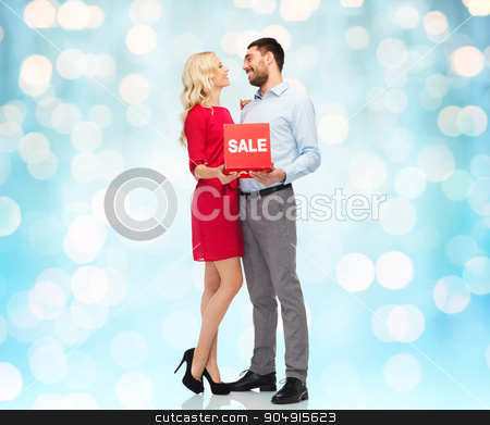 happy couple with red sale sign stock photo, people, sale, discount and christmas concept - happy couple with red sale sign over blue holidays lights background by Syda Productions