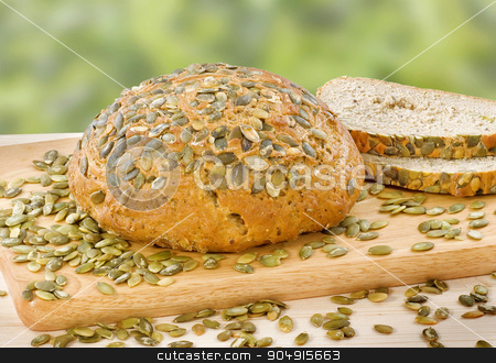 Bread with pumpkin seeds stock photo, Loaf of bread topped with pepitas by Digifoodstock