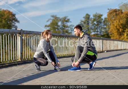 smiling couple tying shoelaces outdoors stock photo, fitness, sport, people and lifestyle concept - smiling couple tying shoelaces outdoors by Syda Productions