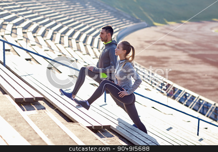 couple stretching leg on stands of stadium stock photo, fitness, sport, exercising and lifestyle concept - couple stretching leg on stands of stadium by Syda Productions