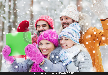 smiling friends with tablet pc in winter forest stock photo, technology, season, friendship and people concept - group of smiling men and women taking selfie tablet pc computer in winter forest by Syda Productions