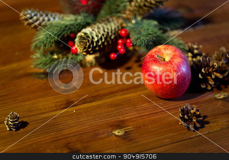 close up of apple with fir decoration on wood stock photo, christmas, decoration, holidays and new year concept - close up of red apple with fir branch decoration on wooden table by Syda Productions