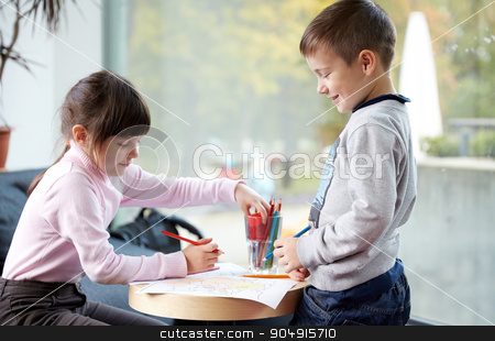 happy little girl and boy drawing at home stock photo, childhood, leisure, friendship and people concept - happy little girl and boy drawing and coloring picture with pencils at home by Syda Productions