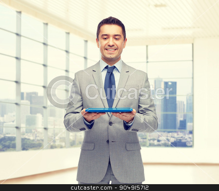 happy businessman in suit holding tablet pc stock photo, business, people and technology concept - happy smiling businessman in suit holding tablet pc computer over office room background by Syda Productions