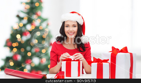 woman in santa helper hat with many gift boxes stock photo, christmas, x-mas, winter, happiness concept - smiling woman in santa helper hat with many gift boxes and wrapping paper by Syda Productions