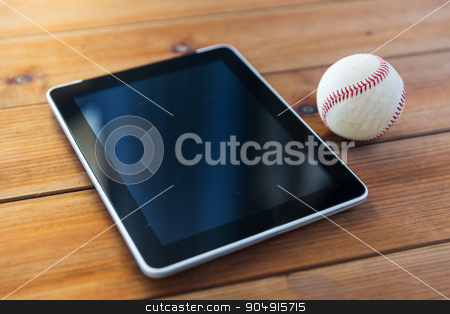 close up of baseball ball and tablet pc on wood stock photo, sport, technology, game and objects concept - close up of baseball ball and tablet pc computer on wooden floor by Syda Productions