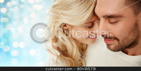 close up of happy couple faces with closed eyes stock photo, family, love, winter and people concept - close up of happy couple faces with closed eyes over blue holidays lights background by Syda Productions