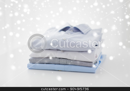 close up of ironed and folded shirts on table stock photo, ironing, laundry, clothes, housekeeping and objects concept - close up of ironed and folded shirts on table at home over snow effect by Syda Productions