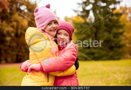 two happy little girls hugging in autumn park stock photo, autumn, childhood, leisure and people concept - two happy little girls hugging in park by Syda Productions