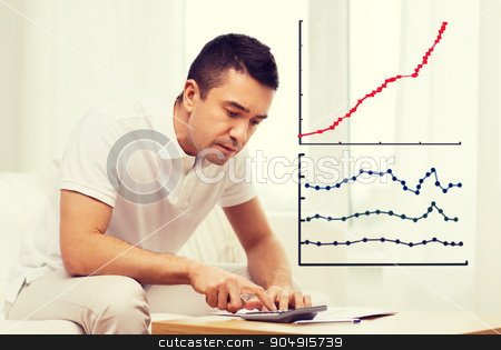 man with papers and calculator at home stock photo, business, savings, finances and people concept - man with papers and calculator at home by Syda Productions