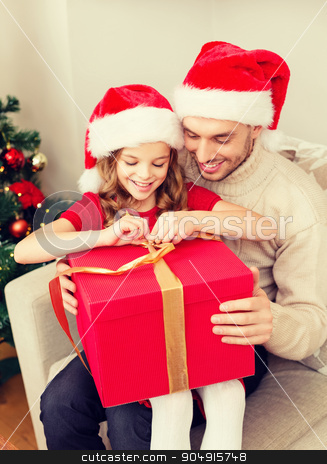 smiling father and daughter opening gift box stock photo, family, christmas, x-mas, happiness and people concept - smiling father and daughter in santa helper hats opening gift box by Syda Productions
