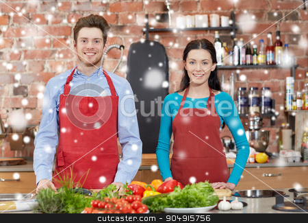 happy couple in kitchen at cooking class stock photo, cooking class, culinary, food and people concept - happy couple in kitchen over snow effect by Syda Productions