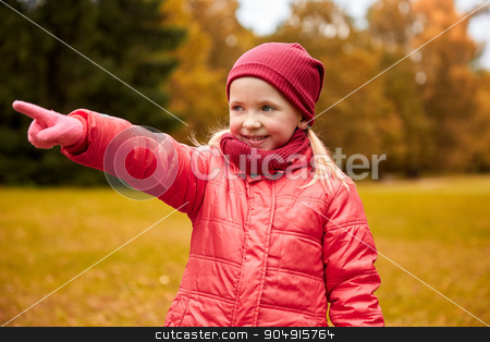 happy little girl pointing finger in autumn park stock photo, autumn, childhood, leisure, gesture and people concept - happy little girl pointing finger to something in autumn park by Syda Productions