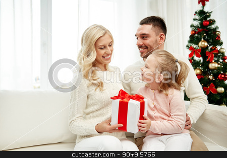 happy family at home with christmas gift box stock photo, family, christmas, holidays and people concept - happy mother, father and little daughter with gift box sitting on sofa at home by Syda Productions