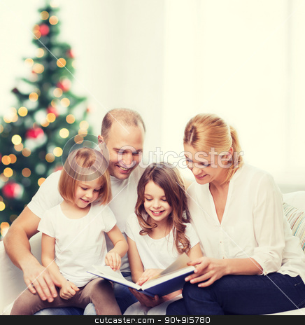happy family with book at home stock photo, family, childhood, holidays and people - smiling mother, father and little girls reading book over living room and christmas tree background by Syda Productions