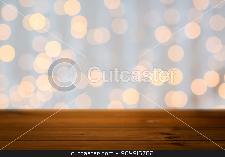 empty wooden table with christmas golden lights stock photo, holidays, new year and celebration concept - close up of empty wooden surface or table over christmas golden lights background by Syda Productions
