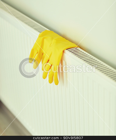 close up of rubber gloves hanging on heater stock photo, protection, housework and housekeeping concept - close up of yellow rubber gloves hanging on heater at home by Syda Productions