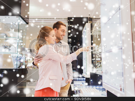 couple looking to shopping window at jewelry store stock photo, sale, consumerism and people concept - happy couple pointing finger to shopping window at jewelry store in mall with snow effect by Syda Productions