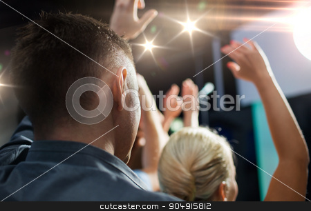close up of happy people at concert in night club stock photo, party, holidays, music, nightlife and people concept - close up of happy people at concert in night club waving hands by Syda Productions
