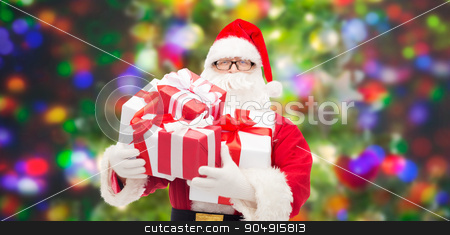 man in costume of santa claus with gift boxes stock photo, christmas, holidays and people concept - man in costume of santa claus with gift boxes over party lights background by Syda Productions