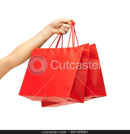 close up of hand holding red shopping bags stock photo, people, sale, consumerism, advertisement and commerce concept - close up of hand holding red blank shopping bags by Syda Productions