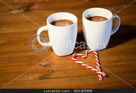 christmas candy canes and cups on wooden table stock photo, holidays, christmas, winter, food and drinks concept - close up of candy canes and cups with hot chocolate or cocoa drinks on wooden table by Syda Productions