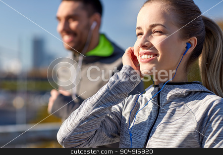 happy couple with earphones running in city stock photo, fitness, sport, people, technology and lifestyle concept - happy couple running and listening to music in earphones at city by Syda Productions