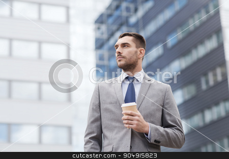 young serious businessman with paper cup outdoors stock photo, business, hot drinks and people and concept - young serious businessman with paper coffee cup over office building by Syda Productions