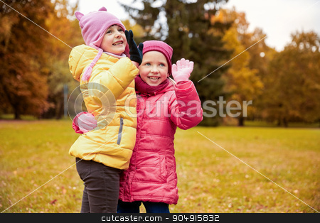 happy little girls waving hands in autumn park stock photo, autumn, childhood, leisure, gesture and people concept - happy little girls waving hands in park outdoors by Syda Productions